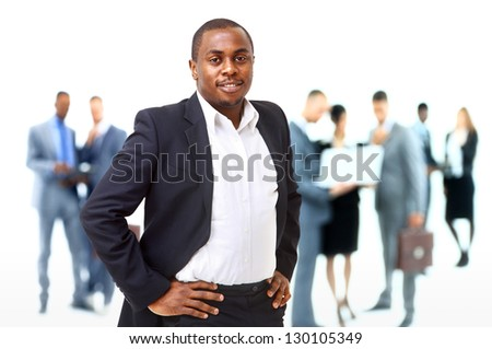 Portrait of smart African American business man smiling with colleagues in background - stock photo