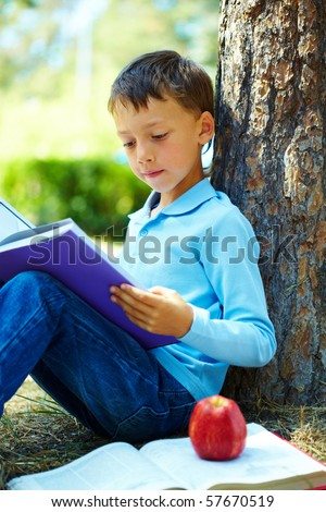 Portrait of smart boy in the park and reading interesting book in free time