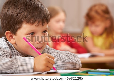 Portrait of smart boy sitting in class and drawing something in copybook while listening to the teacher during lesson - stock photo