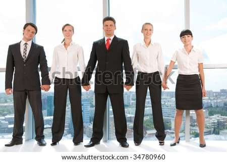 Portrait of smart business group standing in row and looking at camera with smiles