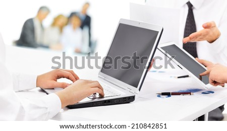 Portrait of smart business partners using laptop at meeting - stock photo