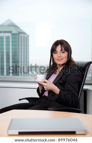 Portrait of smart business woman having cup of coffee at office - stock photo