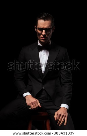 portrait of smart businessman in black suit posing in dark studio background while wearing glasses and looking at the camera - stock photo