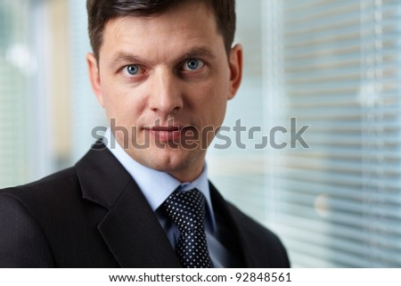 Portrait of smart businessman looking at camera - stock photo