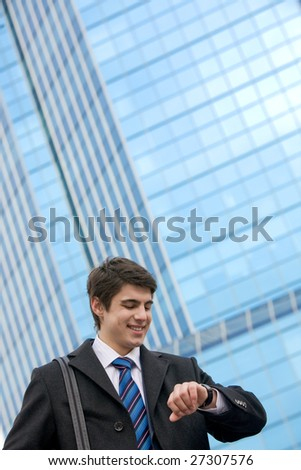 Portrait of smart businessman looking at his watch with happy expression - stock photo