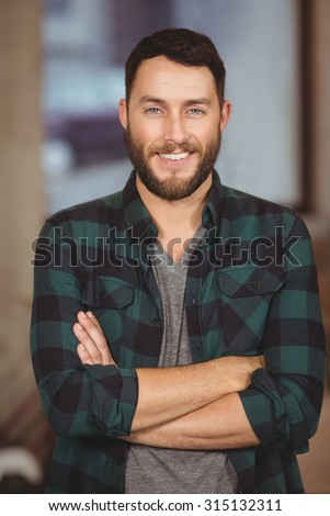 Portrait of smart businessman standing arms crossed in creative office