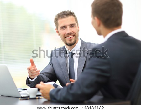 Portrait of smart businessmen discussing project in laptop and tablet at meeting