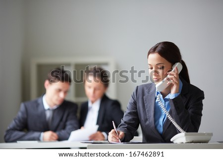 Portrait of smart businesswoman calling on the phone and making notes on background of working colleagues - stock photo