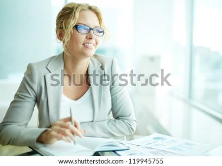 Portrait of smart businesswoman in eyeglasses planning work - stock photo