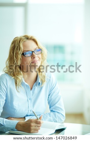 Portrait of smart businesswoman in eyeglasses planning work - stock photo