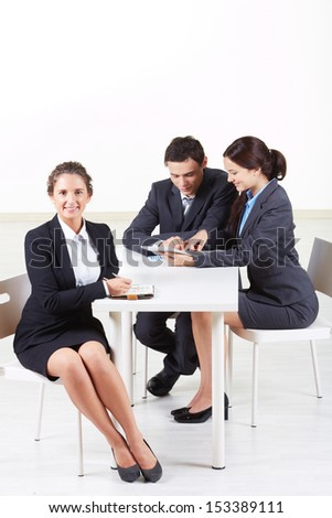 Portrait of smart businesswoman looking at camera on background of working colleagues - stock photo
