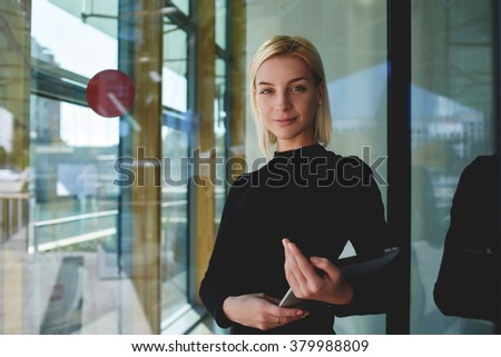 Portrait of smart businesswoman resting after development project on digital tablet while standing near office conference room, successful female financier holding touch pad after her presentation - stock photo