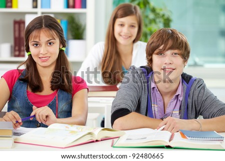 Portrait of smart classmates looking at camera during lesson - stock photo