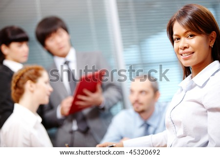 Portrait of smart employer looking at camera on background of people working - stock photo