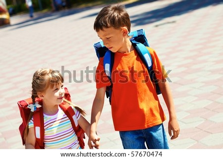 Portrait of smart friends with backpacks walking down city road on sunny day - stock photo