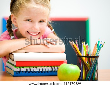 Portrait of smart girl at workplace with the books - stock photo