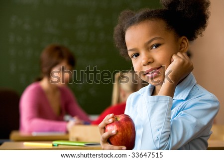 Portrait of smart girl with big red apple smiling at camera - stock photo