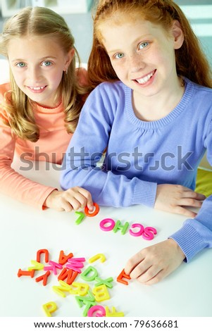 Portrait of smart girls making word ?school? and looking at camera - stock photo