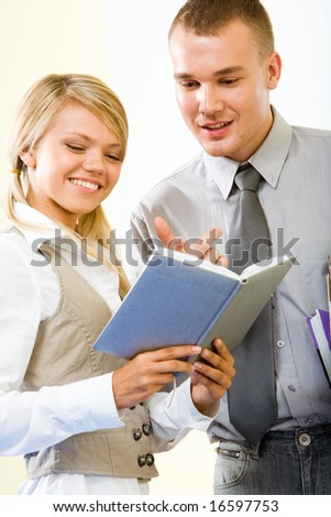 Portrait of smart guy pointing at notebook and explaining something to smiling girl