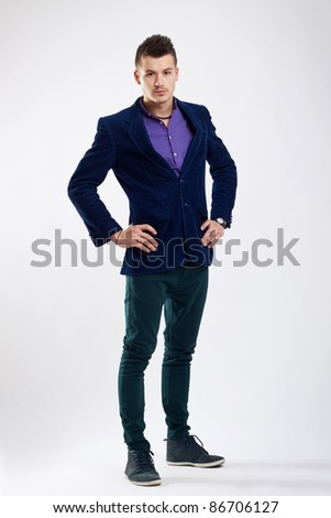 Portrait of smart guy standing with hand on hip on studio background - stock photo