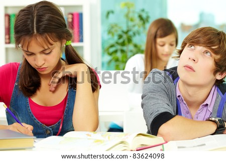 Portrait of smart guy thinking with his classmates near by making notes in copybook