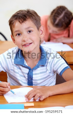 Portrait of smart lad at workplace looking at camera with classmate on background - stock photo