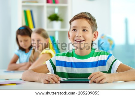Portrait of smart lad at workplace looking at teacher with his classmates on background - stock photo