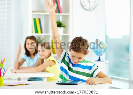Portrait of smart lad at workplace raising hand and looking at touchpad with his classmates on background - stock photo