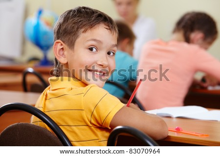 Portrait of smart lad at workplace with classmates on background