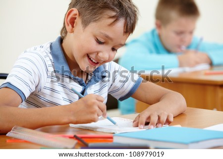 Portrait of smart lad drawing at lesson with classmate on background - stock photo
