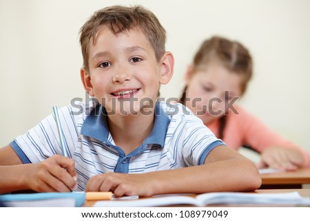 Portrait of smart lad looking at camera with classmate on background - stock photo