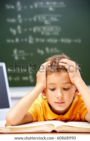 Portrait of smart lad reading at his place - stock photo