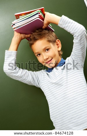 Portrait of smart lad with copybooks on head looking at camera - stock photo