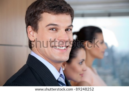 Portrait of smart male entrepreneur standing with his female co-workers - stock photo