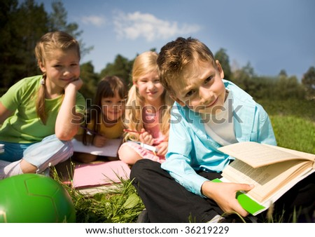 Portrait of smart preschooler holding book with several girls on background in natural environment - stock photo
