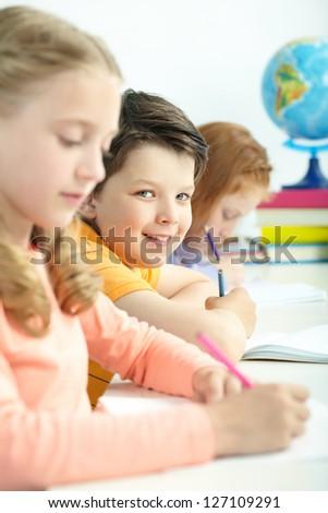 Portrait of smart schoolboy looking at camera between classmates - stock photo
