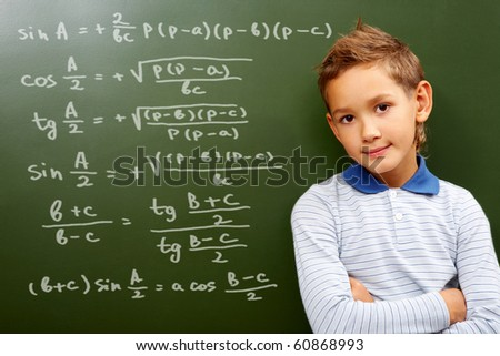 Portrait of smart schoolchild by the blackboard with sums on it looking at camera - stock photo