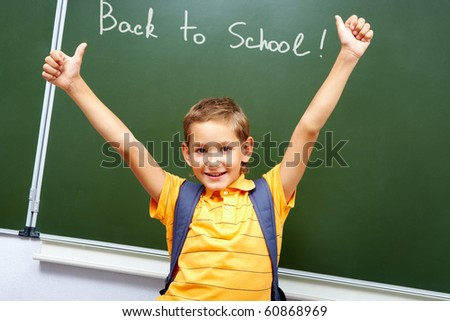 Portrait of smart schoolchild with raised arms by the blackboard looking at camera - stock photo