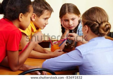 Portrait of smart schoolchildren and their teacher interacting in classroom - stock photo