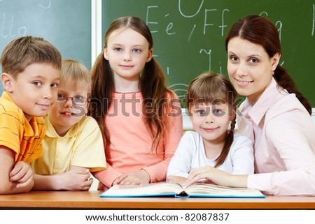 Portrait of smart schoolchildren and their teacher looking at camera in classroom - stock photo