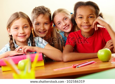 Portrait of smart schoolchildren looking at camera in classroom - stock photo