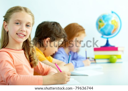 Portrait of smart schoolgirl looking at camera at drawing lesson - stock photo
