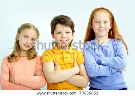 Portrait of smart schoolgirls and schoolboy looking at camera - stock photo