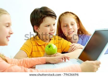 Portrait of smart schoolgirls and schoolboy looking at the laptop screen - stock photo