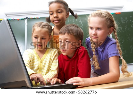 Portrait of smart schoolgirls and schoolboy looking at the laptop with blackboard on background - stock photo