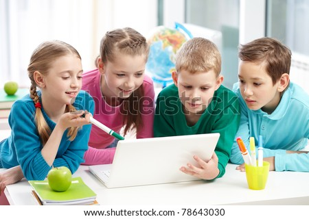 Portrait of smart schoolgirls and schoolboys looking at the laptop in classroom - stock photo
