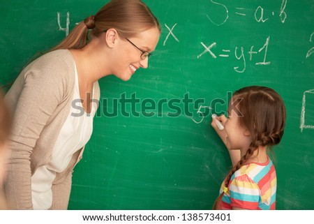 Portrait of smart teacher and schoolgirl standing by blackboard and looking at one another - stock photo
