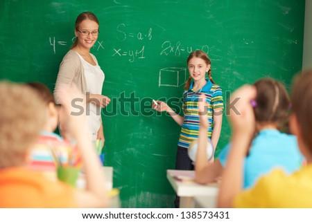 Portrait of smart teacher and schoolgirl standing by blackboard and looking at schoolkids in classroom - stock photo