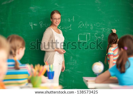 Portrait of smart teacher standing by blackboard and looking at schoolkids while one of pupils writing on blackboard - stock photo
