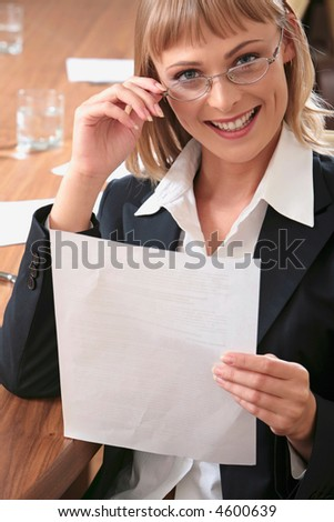Portrait of smart women holding business document and mysteriously smiling